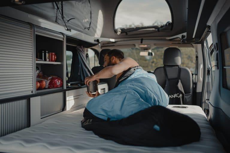 homme allongé dans un van aménagé
