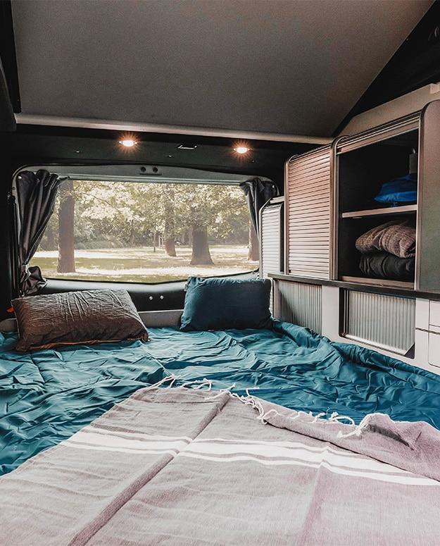 banquette en position couchage van aménagé hanroad avec couvertures et coussins