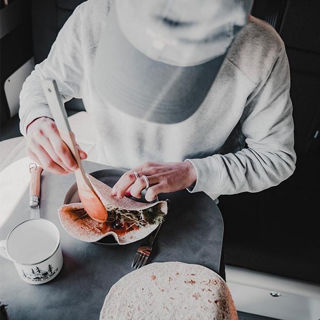 personne préparant un repas dans un van aménagé hanroad sur une table