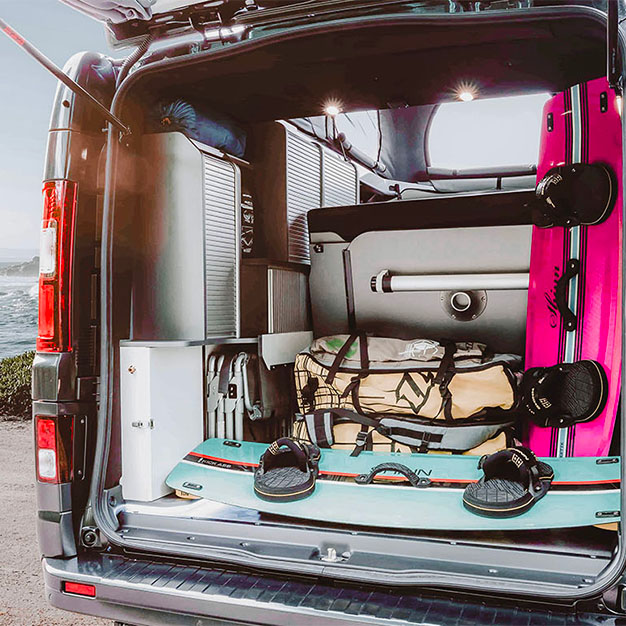 grand coffre d'un van aménagé avec table intégrée et kite surf stocké hanroad