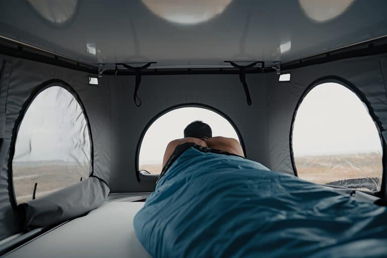 homme dormant dans un lit de toit relevable d'un van aménagé