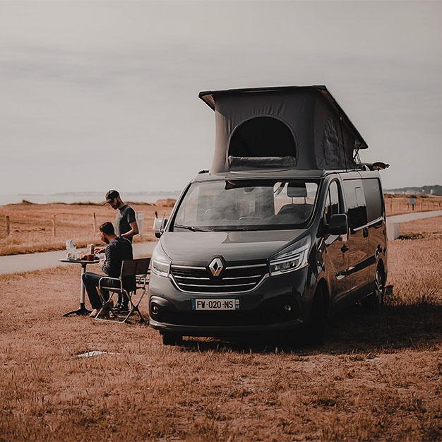vanlifers déjeunant à côté d'un van aménagé hanroad sur porteur renault trafic avec toit relevé